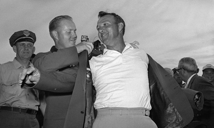 In this April 12, 1964 file photo, Arnold Palmer, right, slips into his green jacket with help from Jack Nicklaus after winning the Masters golf championship, in Augusta, Ga. Fifty years ago, Palmer won the Masters for the fourth time. It was his seventh major. He was 34, the King. (AP Photo/File)