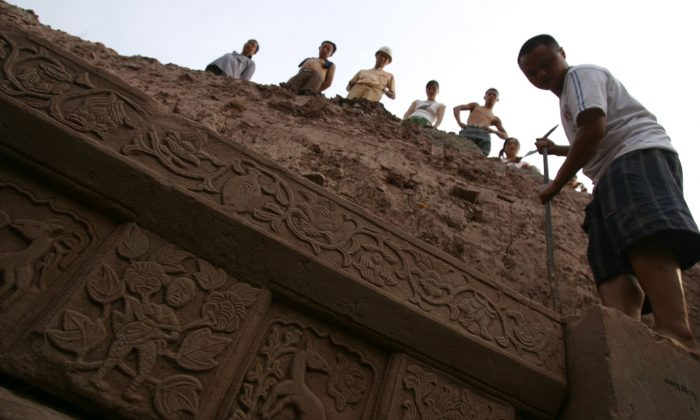 Laborers work on the excavation of a tomb at a construction site at Yubei District in Chongqing on Aug. 28, 2006. (China Photos/Getty Images)
