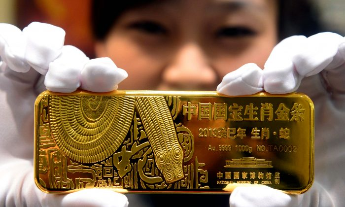 A woman holds a gold bar to mark the year of the snake in Beijing in 2012.  (STR/AFP/Getty Images)