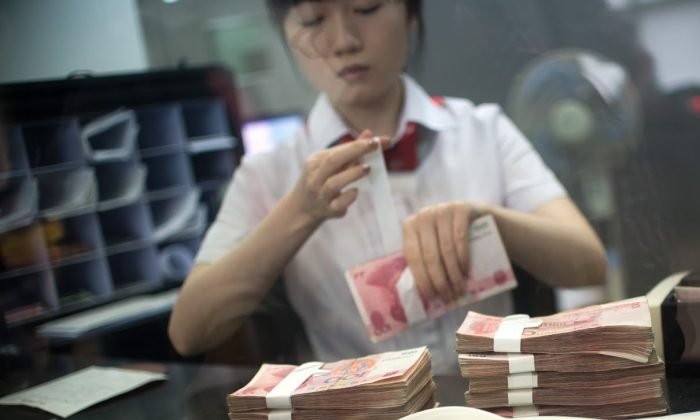 A worker of an Industrial and Commercial Bank of China Ltd (ICBC) branch counts money as she serves a customer on  September 24, 2014. (JOHANNES EISELE/AFP/Getty Images)