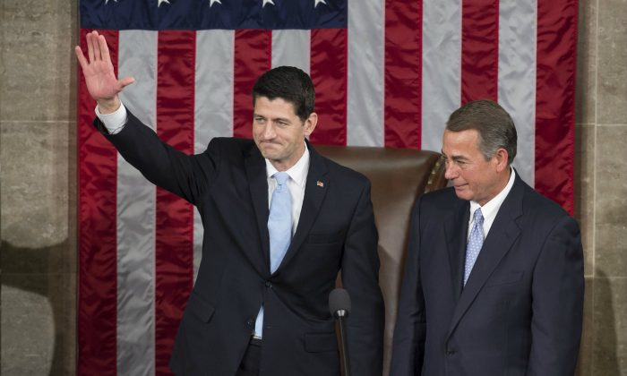 Newly elected Speaker of the House Paul Ryan, Republican of Wisconsin, waves alongside outside Speaker John Boehner, Republican of Ohio, after being elected Speaker in the House Chamber at the US Capitol in Washington, DC, Oct. 29, 2015. (SAUL LOEB/AFP/Getty Images)
