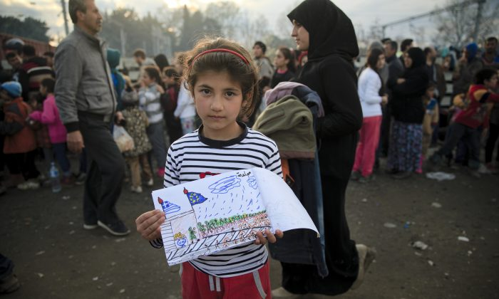 "Shaharzad Hassan, 8 year-old from the Syrian city of Aleppo poses with a drawing she made as people wait in line for food rations at the northern Greek border station of Idomeni, Friday, March 11, 2016. At an overcrowded refugee camp on the Greek-Macedonian border, 8-year-old Shaharzad Hassan draws pictures of the harrowing events in her life over the past 18 months: Pictures of death in her home town of Aleppo, Syria, and her perilous journey to Europe. The title, of this drawing seen at top right reads ""Famine"" .(AP Photo/Vadim Ghirda)"