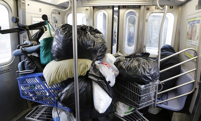 In this March 14, 2016 photo, a homeless man, right, sleeps with his belongings stacked into two shopping carts while riding the subway in New York. (AP Photo/Mark Lennihan)