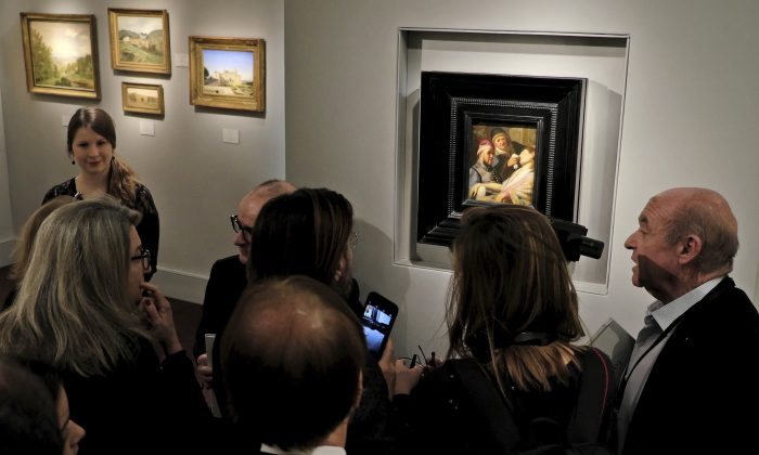 Visitors to the booth of Galerie Talabardon & Gautier at the TEFAF fine art fair look at a newly discovered painting by Dutch master Rembrandt titled The Unconscious Patient (Sense of Smell) dated at around 1624-25, oil on panel 21.6x17.8 cm, in Maastricht, southern Netherlands, Thursday, March 10, 2016. (AP Photo/Mike Corder)