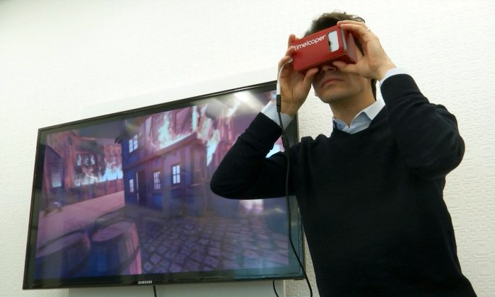 This Feb. 2, 2016 image made from video shows Timelooper co-founder Yigit Yigiter looking through a Google cardboard virtual reality headset as he sees a recreation of the Great Fire of London in 1666. (AP Photo)