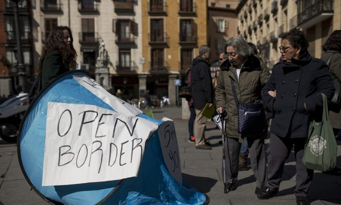 Passers-by look at a tent set up during a symbolic protest against the European Union proposals to deport refugees back to Turkey, in Madrid, Wednesday, March 16, 2016. Leaders of the EU's 28 divided nations plan to reconvene in Brussels this week in hopes of ironing out disagreements on a proposed agreement with Turkey in the migrants crisis. (AP Photo/Francisco Seco)