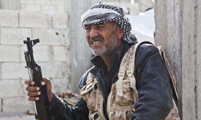 In this Nov. 19, 2014, file photo, a Free Syrian Army fighter takes a break in Kobani, Syria. (AP Photo/Jake Simkin)