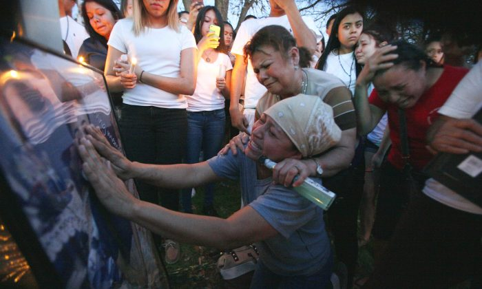 In this March 14, 2016 photo, Ana Henriques places her hands on a portrait of her son Jose Cruz, 16, as she is consoled by friend Norma Velasquez during a candle light vigil for her son, who was shot by an off-duty Farmers Branch police officer, outside a Shell gas station where the shooting occurred in Addison, Texas. (Ben /The Dallas Morning News via AP)