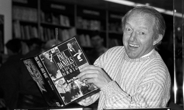 This is a Dec. 2, 1989 file photo of  British magician Paul Daniels as he holds with a copy of his book 'Adult Magic' at Whiteleys book shop in London. Daniels, best known for The Paul Daniels Magic Show that regularly attracted 15 million TV viewers in Britain and was sold to 43 countries, has died after suffering from an inoperable brain tumor. He was 77.  His publicist, Bex Colwell, said, in a statement that Daniels died Thursday March 17, 2016, at his home in Berkshire, 60 miles (95 kms) west of London with his wife by his side.  (PA/File via AP)