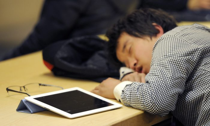 A man takes a nap next to his Ipad at a cafe shop in Beijing on February 22, 2012. (LIU JIN/AFP/Getty Images)