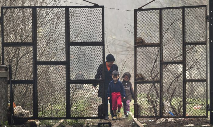 A migrant woman and two kids walk through the gate of a hangar where people have set up their tents at the northern Greek border point of Idomeni, Greece on March 18, 2016.  (AP Photo/Vadim Ghirda)