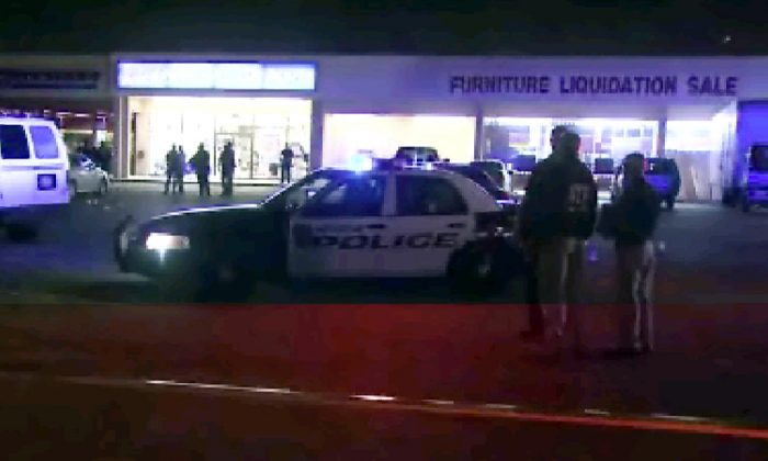 This still image taken from video provided by KPRC shows police responding to the scene of a shooting, Thursday, March 17, 2015 in Houston.  Police fired at five suspected robbers Thursday night outside the furniture store, killing two and injuring two other members of the group, which was being monitored by a tactical team investigating other robberies earlier in the day. (KPRC via AP) MANDATORY COURTESY KPRC, NO ACCESS HOUSTON MARKET LOCAL TV OUT