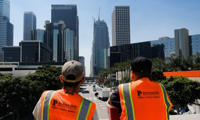 Maintenance workers look down South Figueroa Street toward a skyscraper under construction where a worker fell to his death on Thursday, March 17, 2016. A fire department spokesperson said the the construction worker plunged 50 stories to his death from the Wilshire Grand Tower on South Figueroa Street and hit the back of a passing car in downtown Los Angeles. (AP Photo/Richard Vogel)
