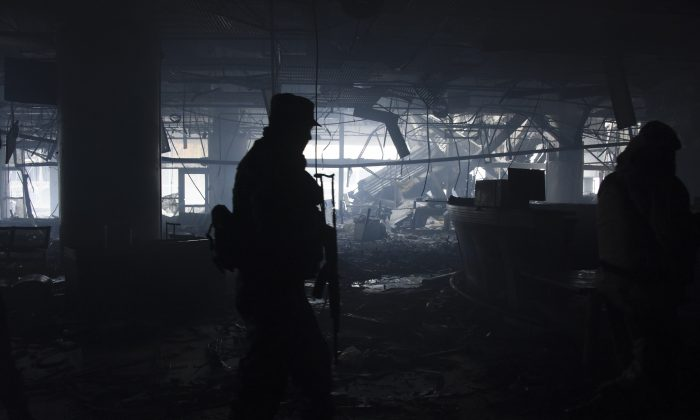 Russia-backed rebels walk in the destroyed building of Donetsk Airport just outside Donetsk, eastern Ukraine, on April 2, 2015. OSCE monitors accompanied by pro-Russian rebels visited the ruins of Donetsk Airport and nearby areas to monitor the situation on the ground and discuss the observance of February's cease-fire. (AP Photo/Mstyslav Chernov)