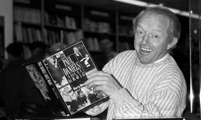 """British magician Paul Daniels as he holds with a copy of his book """"Adult Magic"""" at Whiteleys book shop in London on Dec. 2, 1989. Daniels, best known for The Paul Daniels Magic Show that regularly attracted 15 million TV viewers in Britain and was sold to 43 countries, has died after suffering from an inoperable brain tumor. He was 77. His publicist, Bex Colwell, said, in a statement that Daniels died Thursday, March 17, 2016, at his home in Berkshire, 60 miles west of London with his wife by his side. (PA via AP)"""