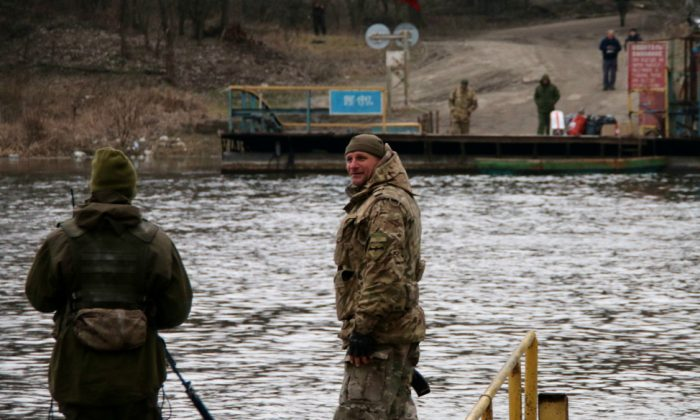 Ukrainian soldiers at the ferry crossing in Lobacheve keep an eye on separatist troops on the opposite shore. (Nolan Peterson/The Daily Signal)