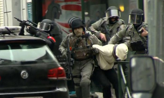 Armed police officers escort Salah Abdeslam to a police vehicle during a raid in the Molenbeek neighborhood of Brussels, Belgium, on March 18, 2016. (VTM via AP) BELGIUM OUT