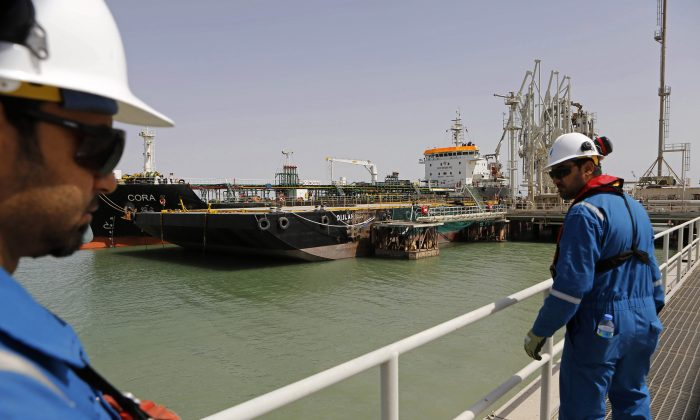 Iraqi engineers observe a gas carrier as it prepares to set sail at the southern port of Umm Qasr near Basra, Iraq, on March 20, 2016. A government spokesman says Iraq has exported the first shipment of natural gas condensate in its history, a key development for the OPEC member struggling to feed a cash-strapped economy amid an expensive fight against the Islamic State. (AP Photo/Nabil al-Jurani)