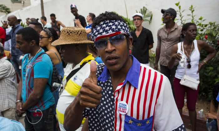 A man wearing a shirt and head scarf with a Stars and Stripes motif flashes a thumbs up at a weekly rumba dance gathering in Havana, Cuba, on March 19, 2016. President Barack Obama will travel to the communist island March 20. During his three-day trip, the first to the country by a sitting president in nearly 90 years he will meet with President Raul Castro at the Palace of the Revolution and attend a baseball exhibition game. (AP Photo/Desmond Boylan)