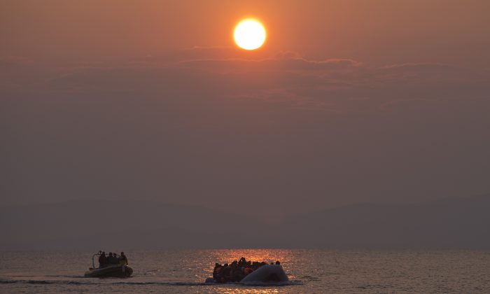 The sun rises as migrants and refugees on a dingy arrive at the shore of the northeastern Greek island of Lesbos, after crossing the Aegean sea from Turkey on March 20, 2016. In another incident two Syrian refugees have been found dead on a boat on the first day of the implementation of an agreement between the EU and Turkey on handling the new arrivals. (AP Photo/Petros Giannakouris)