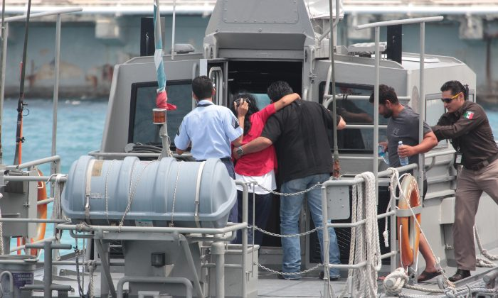 """Mexican Navy personnel help Cuban migrants after being rescued in Cozumel, Mexico, on March 19, 2016. According to a U.S Coast Guard news release, """"18 reported Cuban migrants were picked up by the Royal Caribbean's Brilliance of the Seas cruise ship west of Marco Island, Fla. The 18 migrants were reportedly suffering from severe dehydration and claimed they left Cuba 22 days ago where nine of the migrants perished at sea during the journey."""" (Angel Villegas via AP)"""