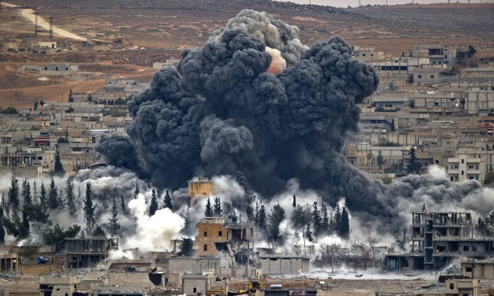 Smoke rises from the Syrian city of Kobani, following an airstrike by the U.S.-led coalition, seen from a hilltop outside Suruc, on the Turkey-Syria border, on Nov. 17, 2014. After months of losing ground in Iraq and Syria, the Islamic State is showing signs of the wear and tear, with commanders on the ground saying they are seeing an increase in desertions. But the jihadis appear to be lashing back with more terrorist and chemical attacks. (AP Photo/Vadim Ghirda)