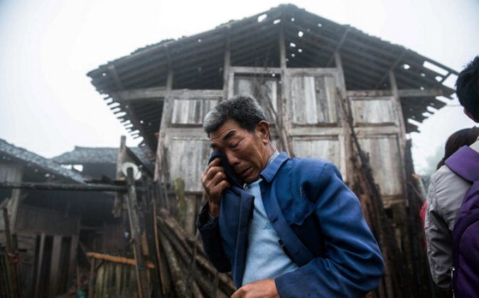 An elderly man crying in front of a damaged house in a remote village in the earthquake-affected Ya'an region of southwest China on April 23, 2013. (STR/AFP/Getty Images)