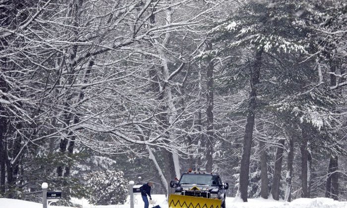 A snowplow truck passes a shoveler, Monday, March 21, 2016, in North Andover, Mass. Steady snowfall made for a sloppy Monday morning commute across much of New England. (AP Photo/Elise Amendola)