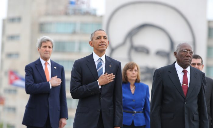 U.S. President Barack Obama, center, and Secretary of State John Kerry, left, listen to the U.S. national anthem during a ceremony at the Jose Marti monument in Revolution Square in Havana, Cuba,  Monday, March 21, 2016.  (AP Photo/Enric Marti)