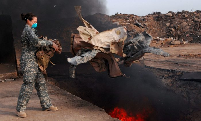 U.S. Air Force Senior Airman Frances Gavalis, 332nd Expeditionary Logistics Readiness Squadron equipment manager, tosses unserviceable uniform items into a burn pit at Balad Air Base, Iraq, on March 10, 2008. Military uniform items turned in must be burned to ensure they cannot be used by opposing forces. (U.S. Department of Defense, Public Domain)