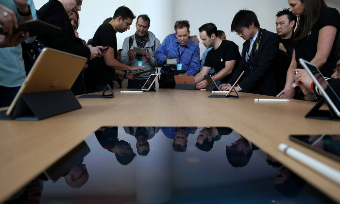 "CUPERTINO, CA - MARCH 21:  Attendees look at the new 9.7"" iPad Pro during an Apple special event at the Apple headquarters on March 21, 2016 in Cupertino, California. Apple CEO announced the iPhone SE and a 9.7"" version of the iPad Pro.  (Photo by Justin Sullivan/Getty Images)"