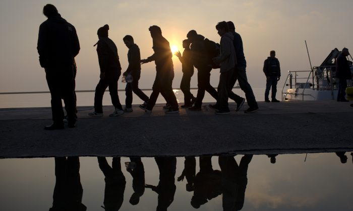 Migrants are reflected in a water puddle as they disembark off the coast of the Greek island of Lesbos on March 21, 2016. (Petros Giannakouris/AP Photo)
