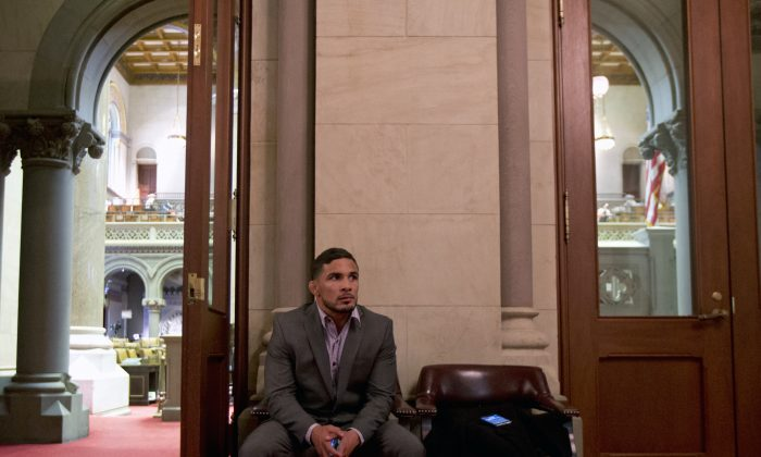 FILE- In this March 3, 2015, file photo, Mixed martial arts fighter Dennis Bermudez waits to visit Assembly Speaker Carl Heastie at the Capitol in Albany, N.Y. The New York Assembly plans to vote this week on its ban on professional mixed martial arts, following years of leaving the ban intact after critics complained the sport is too violent. (AP Photo/Mike Groll, File)