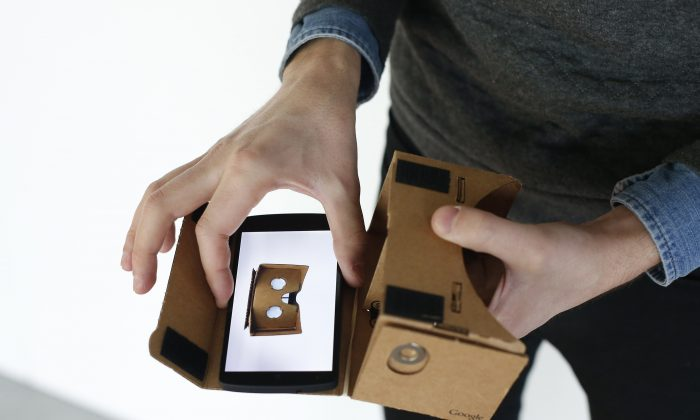 A Google employee presents a Google Cardboard virtual reality headset for android smartphones during a Google promotion event at the City of Fashion and Design (Cite de la mode et du design) in Paris on November 4, 2014. AFP PHOTO / THOMAS SAMSON        (Photo credit should read THOMAS SAMSON/AFP/Getty Images)