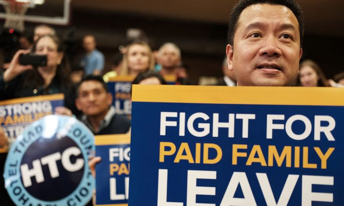 Supporters watch as N.Y. Gov. Andrew Cuomo speaks to promote his paid family leave initiative at a rally in Manhattan, New York City, on March 10, 2016. (Spencer Platt/Getty Images)