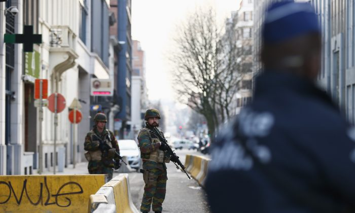 BRUSSELS, BELGIUM - MARCH 22: Soldiers and police officers stand guard outside EU Commission Headquarters following todays attack on March 22, 2016 in Brussels, Belgium. At least 34 people are thought to have been killed after Brussels airport and a Metro station were targeted by explosions. The attacks come just days after a key suspect in the Paris attacks, Salah Abdeslam, was captured in Brussels.  (Photo by Carl Court/Getty Images)