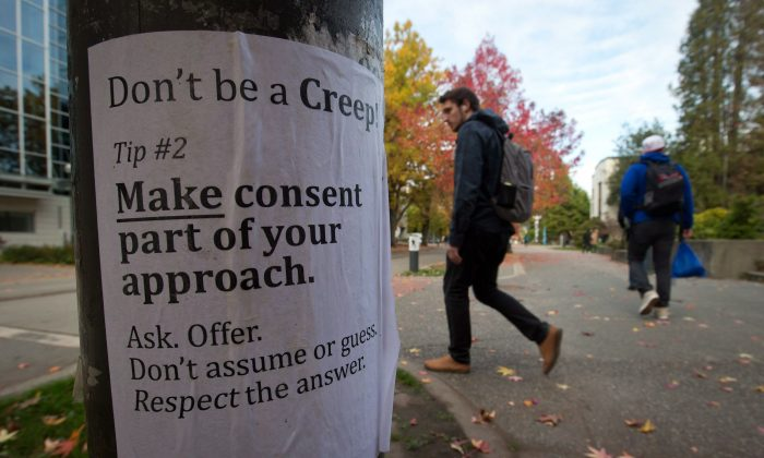 University of British Columbia students walk past a sexual assault poster on the campus in Vancouver on Oct. 30, 2013. (The Canadian Press/Darryl Dyck)