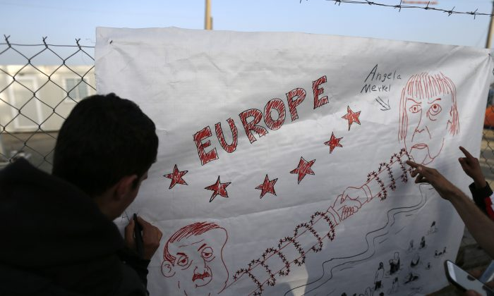 A migrant prepares a banner depicting German Chancellor Angela Merkel, right and Turkey's President Recep Tayyip Erdogan, during a protest demanding the opening of the border between Greece and Macedonia in the northern Greek border station of Idomeni, Greece, Tuesday, March 22, 2016. Greece detained hundreds of refugees and migrants on its islands Monday, as officials in Athens and the European Union conceded a much-heralded agreement to send thousands of asylum-seekers back to Turkey is facing delays. (AP Photo/Darko Vojinovic)