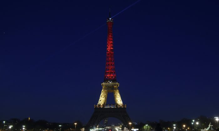 A picture taken on March 22, 2016 shows the Eiffel Tower in Paris illuminated in colours of the Belgian flag in tribute to the victims of terrorist attacks in Brussels. (LIONEL BONAVENTURE/AFP/Getty Images)