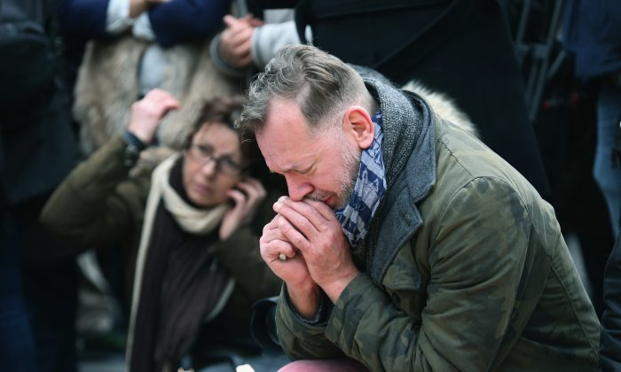People observe a one minute silence at the Place De La Bourse in honour of the victims of yesterdays' terror attacks, in Brussels, Belgium, on March 23, 2016. (Christopher Furlong/Getty Images)