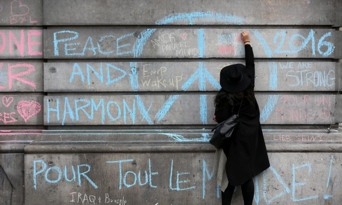 A woman writes a messages of support on the walls of the Bourse De Brussels building in the Place de la Bourse following yesterday's terrorists attacks, in Brussels, Belgium, on March 23, 2016. (Christopher Furlong/Getty Images)