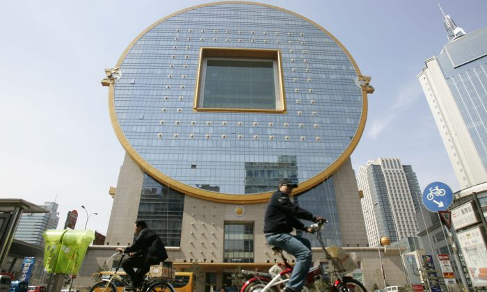 People pedal past a building shaped as a Chinese ancient coin on April 21, 2007 in Shenyang of Liaoning Province, China. (China Photos/Getty Images)