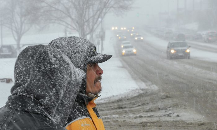 Two men walk in the snow in downtown Sioux Falls, S.D., Wednesday, March 23, 2016. A powerful spring blizzard stranded travelers at Denver's airport and shut down hundreds of miles of highway in Colorado, Wyoming and Nebraska as it spread into the Midwest on Wednesday. (AP Photo/Nati Harnik)