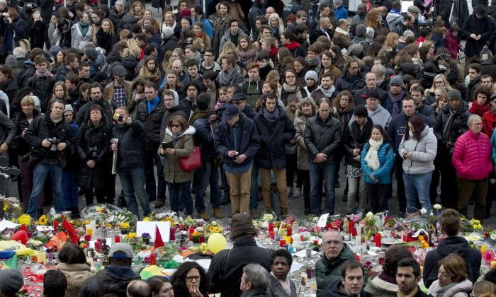 People gathered to observe a minute of silence and mourn for the victims of the bombings at the Place de la Bourse in the center of Brussels, Belgium, Thursday, March 24, 2016. (AP Photo/Peter Dejong)