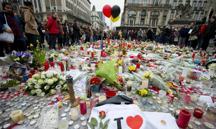 Three balloons in the colors of the Belgian flag fly as people mourn for the victims of the bombings at the Place de la Bourse in the center of Brussels, Belgium, on March 24. (AP Photo/Peter Dejong)