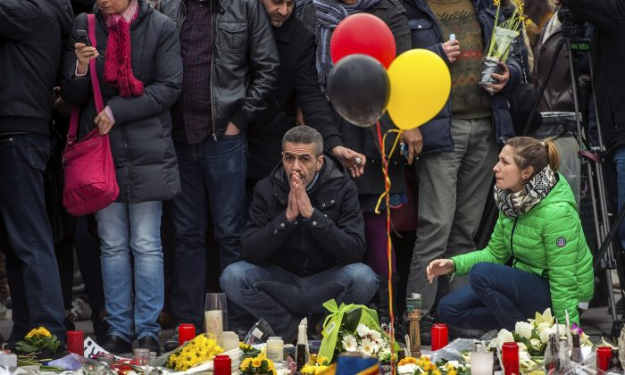 A man sits in front of a makeshift memorial to pay tribute to the victims of the Brussels attacks on the Place de la Bourse (Beursplein) in central Brussels, on March 24, 2016. (Phillipe Huguen/AFP/Getty Images)