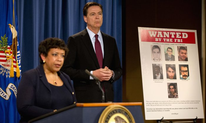 Attorney General Loretta Lynch, and FBI Director James Comey stand by a wanted poster of Iranians who are wanted by the FBI for computer hacking during a news conference at the Justice Department in Washington, Thursday, March 24, 2016. Seven hackers tied to the Iranian government were charged Thursday in a series of punishing cyberattacks on a small dam outside New York City and on dozens of banks _ intrusions that reached into American infrastructure and disrupted the financial system, U.S. law enforcement officials said. (AP Photo/Jacquelyn Martin)