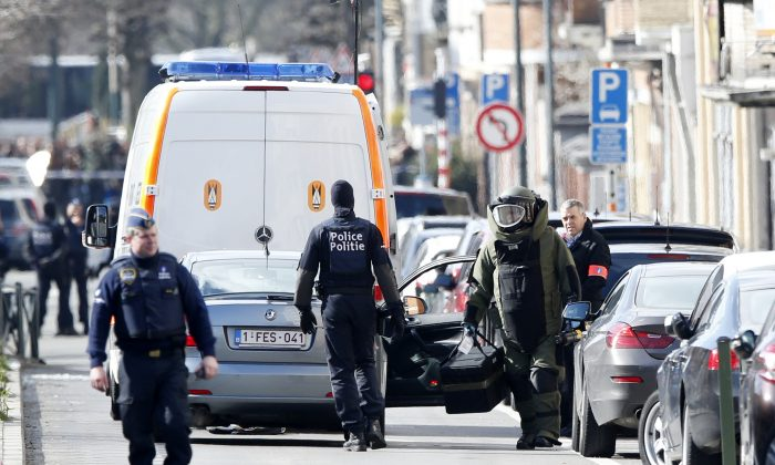 A member of emergency services wearing protective clothing, at right, investigates the scene in Schaerbeek, Belgium, Friday March 25, 2016. (AP Photo/Alastair Grant)