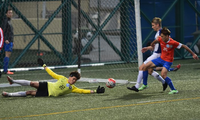 Frederick Schipper of HKFC (blue and white kit) scores in the HKFA First Division match against Kwun Tong at Sports Road on Sunday March 20,2016. HKFC won the match 6-0. (Bill Cox/Epoch Times)