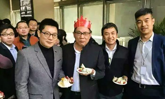 Ren Zhiqiang wearing a birthday hat, holding a cake at his 65 birthday party on March 8, 2016. (Internet image)
